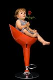 Little girl on swivel chair. Little girl sitting on red swivel chair, offering a rose to someone - concept for mothers day - isolated on black stock photos