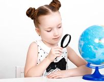 Funny little girl at the table of a first-grader. Royalty Free Stock Images