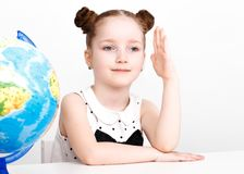 Funny little girl at the table of a first-grader. Stock Photos