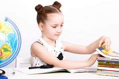 Funny little girl at the table of a first-grader. Royalty Free Stock Photo