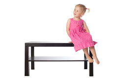Little girl on the table isolated Royalty Free Stock Photos