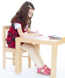 Little girl at the table picturing. Royalty Free Stock Image