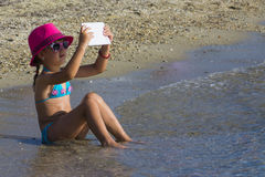 Little girl with tablet on beach during summer vacation Stock Photos