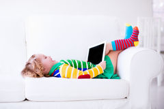 Little girl with tablet computer on a white couch stock image