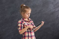Little girl with tablet on dark background. Little girl playing online games on tablet. Female child posing on dark background. Social networking and online Royalty Free Stock Image