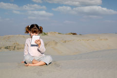 Little girl with tablet in desert Stock Photos