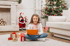 Little girl with tablet and gifts. In christmas decorated living room royalty free stock images