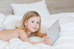 Little girl with a tablet. In hands Royalty Free Stock Photos