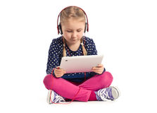 Little girl with tablet and headphones Stock Photo