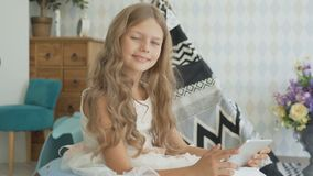 Little girl with tablet at home. Child girl playing computer games stock footage