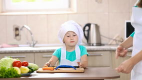 Little girl with a tablet in the kitchen stock video