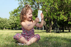 Little girl with tablet in park Stock Images
