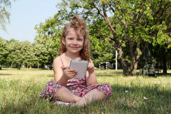 Little girl with tablet in park Stock Photos