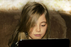 Little girl with tablet PC. At home Stock Photography