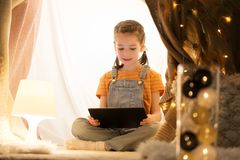 Little girl with tablet pc in kids tent at home. Childhood, technology and hygge concept - happy little girl with tablet pc computer in kids tent at home Royalty Free Stock Photo