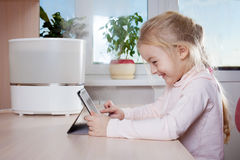 Little girl with tablet pc sitting near humidifier and smiling Stock Photo