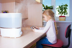 Little girl with tablet pc sitting near humidifier Royalty Free Stock Image