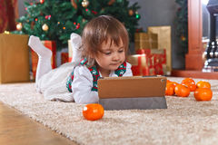 Little girl with tablet in the room with Christmas decorations Stock Photo