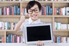 Little girl with tablet shows thumb up Royalty Free Stock Image