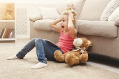 Little girl with tablet sitting on the floor at home. Surprised little girl playing online games on tablet. Female child sitting on the floor near sofa with her Stock Photography