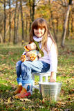 Little girl with taburet, teddy dog and bucket Royalty Free Stock Images