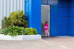 Little girl with tails knocking on steel door Stock Photography