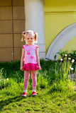 Little girl with tails stands on lawn Stock Photography