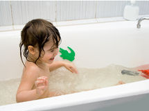 Little girl take a bath. With toys Stock Images