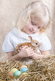 Little girl takes care of the Easter rabbit Stock Image