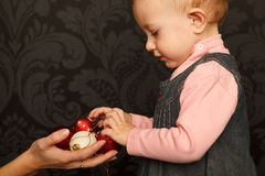 Little girl takes Christmas toys from hands Stock Photos