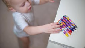 Little girl takes a crayon from a shelf and carries it away