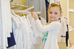 Little girl takes hanger with skirt from stand Royalty Free Stock Photography