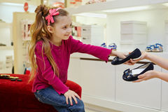 Little girl takes pair of shoes from hands of seller Royalty Free Stock Images