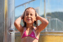 Little girl takes shower after swimming. Little girl dressed in pink swimsuit  takes shower after swimming Royalty Free Stock Photo