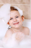 Little girl is taking a bath. With a foam Royalty Free Stock Photos