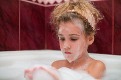 Little girl taking a bath with foam. On his face stock photos