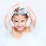 Little girl is taking a bath. Happy little girl is taking a bath with a foam Stock Photography