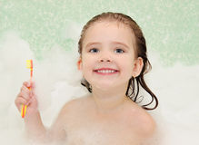 Little girl is taking a bath holding toothbrush. Cute smiling little girl is taking a bath holding toothbrush Stock Photo