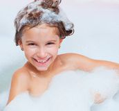 Little girl is taking a bath. Small happy girl is taking a bath with a foam Stock Photos