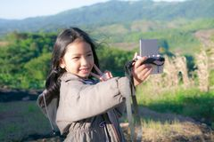 A little girl is taking a camera for selfie royalty free stock images