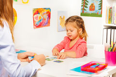 Little girl taking cards from table in the class Royalty Free Stock Photos