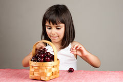 Little girl taking a cherry from a basket Royalty Free Stock Photos