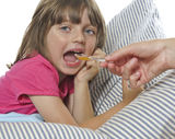 Little girl taking cough syrup fom her mother. Ill little girl taking cough syrup fom her mother - white background Stock Photos