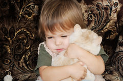Little girl taking in her arms cat Stock Image