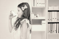 Little girl taking inhaler Stock Images