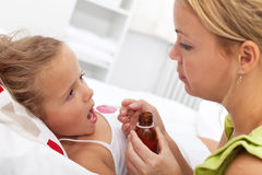 Little girl taking medicine Royalty Free Stock Images