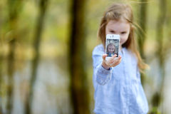 Little girl taking a photo of herself Royalty Free Stock Photography