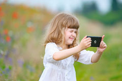 Little girl is taking photo with mobile phone camera outdoor in. Nature Royalty Free Stock Photos