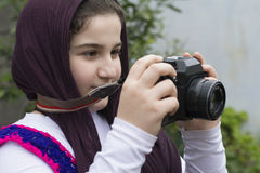 Little Girl Is Taking Photograph by An old Analogue Camera Strap. Young Little Girl Is Taking Photograph by An old Analogue Camera Strapped on Her Neck Stock Image