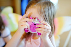 Little girl taking a picture with a toy camera Royalty Free Stock Images